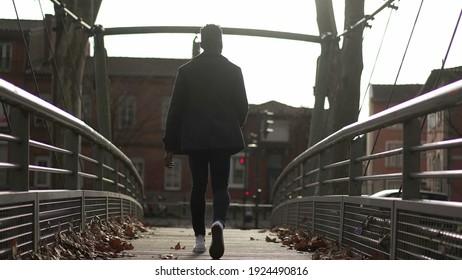 Back of black African man walking outside in urban city