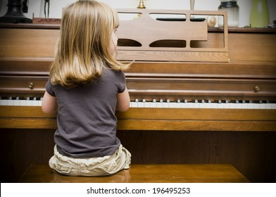 The back of a blond girl, sitting playing a brown, wooden piano.