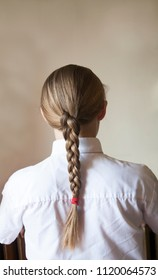 back of blond head with white shirt and plait against pale background with room for text