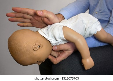 Back blows (the Heimlich maneuver or Heimlich manoeuvre) on a simulation mannequin infant dummy during medical training Basic Life Support