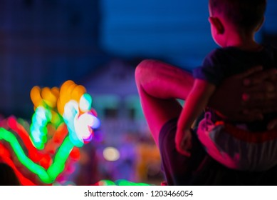 Back blurred portrait of little boy sits on his father's shoulder and watch the lighting dragon in the parade