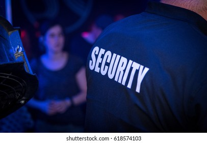 Back of a bouncer (security guard) in a nightclub during a party.