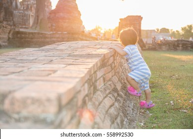 Back of a boy climbing on ancient remains