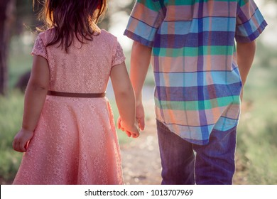 back of boy and girl walking ouside holding hands in dress and easter clothes.jpg