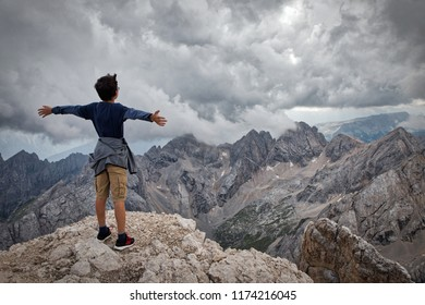 Back of a boy standing with spread hands looking at the stormy clouds conjuring above the mountain range, standing on Marmolada mountain of the Dolomites, Italy. Concept of tourism, travel.