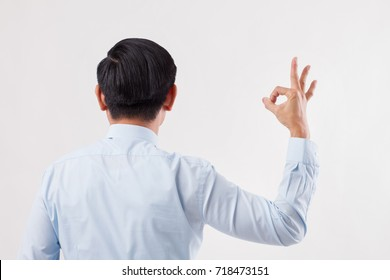 back of business man pointing ok hand sign to blank space
