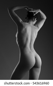 back and butt naked women . naked woman against black background.