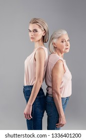 Back to back. Categorical short-haired ladies of different age looking serious while connecting their backs