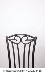 The back of a chair on a white background.