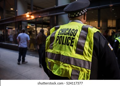 The back of a Chicago police officer controlling the crowd at a rally downtown in Chicago, IL wearing a yellow reflective vest on a sunny day by the tracks in the Loop.