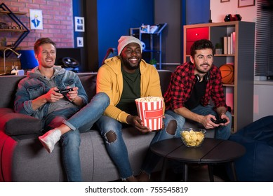 Back to childhood. Cheerful young men are sitting on sofa and expressing gladness. African guy is sitting with popcorn while his friends enjoying play station. They are looking at screen with smile