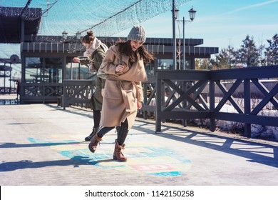Back to childhood. Two women jumping on the pavement playing hopscotch.