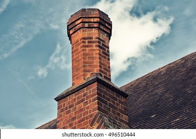 Back of a chimney with blue clouds and whispy clouds