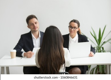Back close up view of female applicant being interviewed by two HR managers reading her resume, checking data on laptop, asking questions for job position. Employment, hiring, first impression concept
