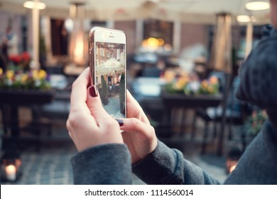 Back close up view of female person holding cellphone with and make photo with street on background. Woman's hands with mobile phone devise, finger touching display