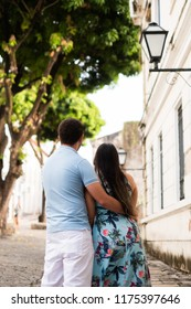 Back couple hugged on cobbled street in a historic city with tree and old light fixture