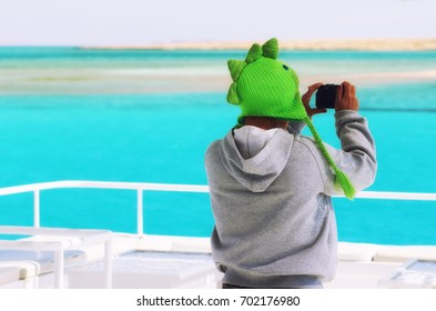 Back of diver girl wearing funky green crest hat taking photos of amazing beautiful Red Sea from boat. Outdoors activities, life style. Taken in Sharm-el-Sheikh, Egypt