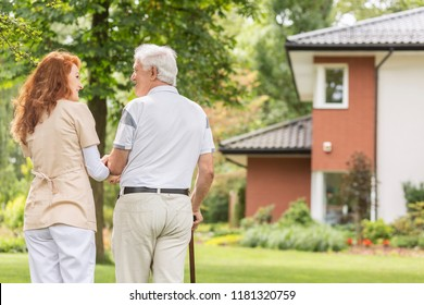 A back of an elderly gray-haired man with a cane and his redhead caretaker while walking in the garden on a sunny afternoon.