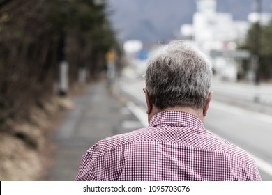 The back of an elderly man's head as he walks away.