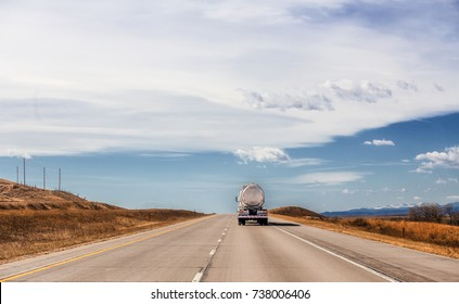 The back end of a oil tanker truck travelling down a interstate in a brown hilly countryside spring landscape