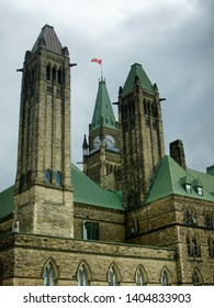 Back facade of the Ottawa Parliament government building complex, Clock Tower and Canadian Flag visible.  Cloudy sky above.