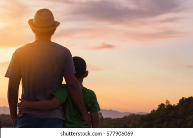 Back of father and son and sunset view.Dark tone