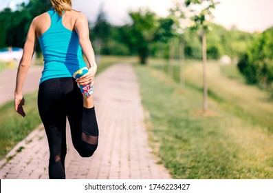 Back of a female runner in sportswear stretching leg, standing on the running track in the nature.
