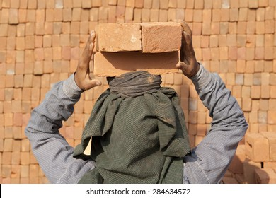 Back of Female worker carry brick on her head,Myanmar