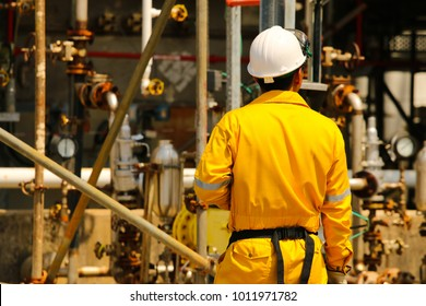 Back of a field operator wearing yellow coverall with petrochemical plant in the background.