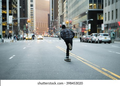 Back figure of young skateboarder cruising donw the city street before sunset. Photographed in New York City in Feb 2016.
