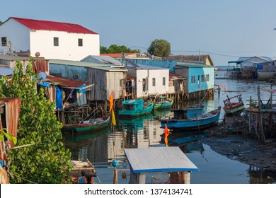 Back of fishermens house and fishing boats on a calm little river in low tide water in the little fishing village Ham Ninh on Phu Quoc Island, Vietnam.