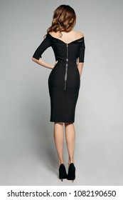 Back full length of stunning slim model with brunette hair wearing elegant black dress with bare shoulders and zip and black high heels. Cutout on grey. Studio.