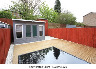 back garden area with bespoke hut and wooden decking, white pebble dash stones, trees and wooden fence on a clear day.