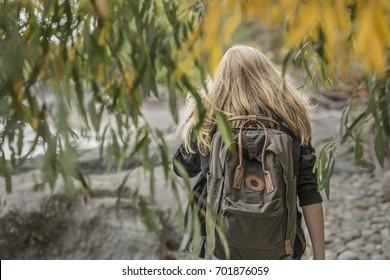 Back of a girl with blonde hair wearing a backpack walking