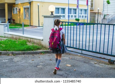 Back of girl child going to school with back pack