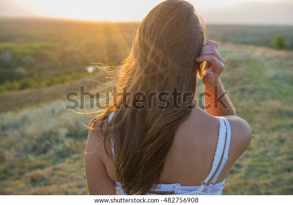 Back Girl in a Meadow At Sunset. Outdoor. Girl walking.