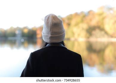 Back of a girl wearing beanie hat. She is looking at the view of the park in autumn