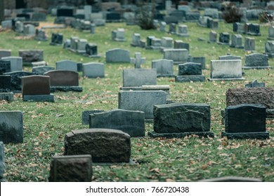 Back of Gravestones in a Old Cemetery during Cold day of Autumn