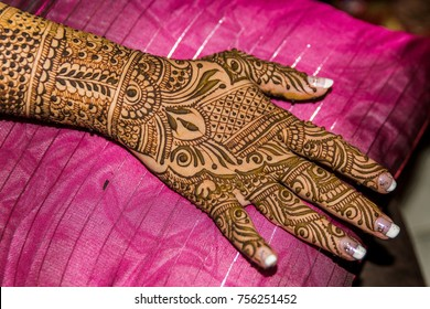 Back of hand, fingers and forearm of Indian bride resting while mehndi is drying. The intricate design, painted using henna paste, takes time to apply and dry. Traditional temporary body art, tattoo.