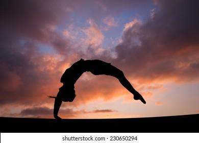 back handspring of female gymnast in sunset sky