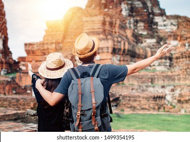 Back of Happy Asian male and female couple traveller carrying backpack with summer hat put hands up  inside historical buddhist ruins heritage in Ayutthaya, Thailand