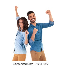back to back happy couple celebrating victory with hands in the air on white background
