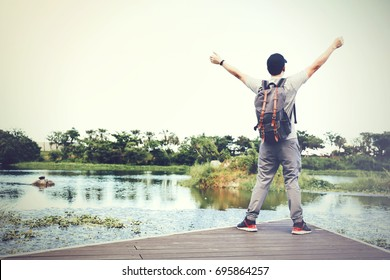 Back of happy and winning travel backpacker raising hands in countryside nature scene