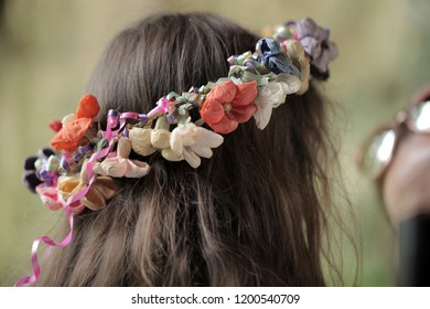 back of a head of a brown hair small caucasian girl, with colorful fake paper flowers coronet, outdoors on a sunny summer day in Poland, Europe