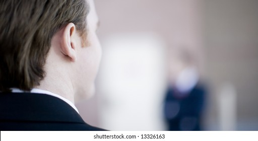 back of the head of a businessman looking at another businessman