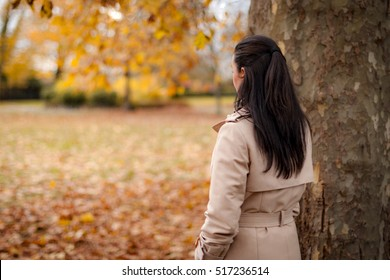 Back of the head image of a mature woman wearing a trench coat in the park watching the fall foliage in autumn with copy space