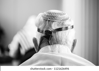 """Back of head of older Jewish man donning leather straps called """"Tefillin"""" in Judaism in black and white"""