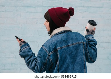 back hipster young girl in a blue denim jacket, which is holding a coffee and looking at phone on a light blue background