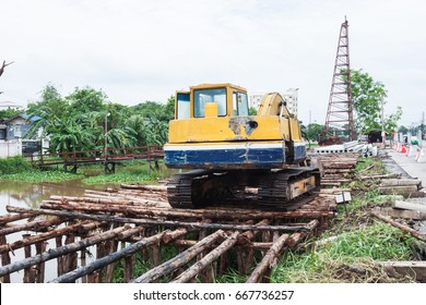 back hoe with concrete footings for river with retaining wall