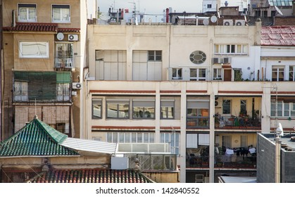 Back of homes in Barcelona with balconies covered with plants, furniture and laundry
